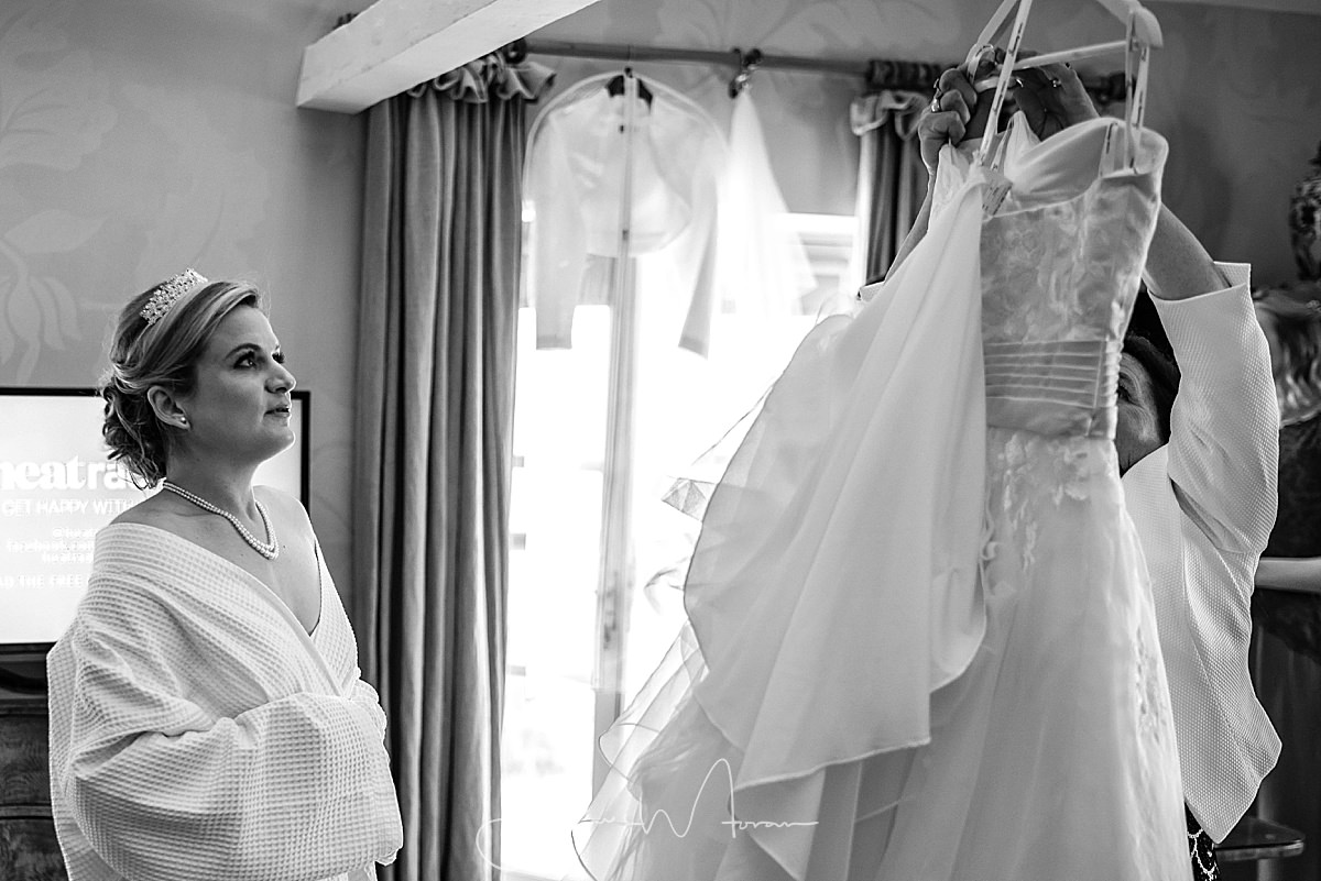 Bride looking at her hanging dress