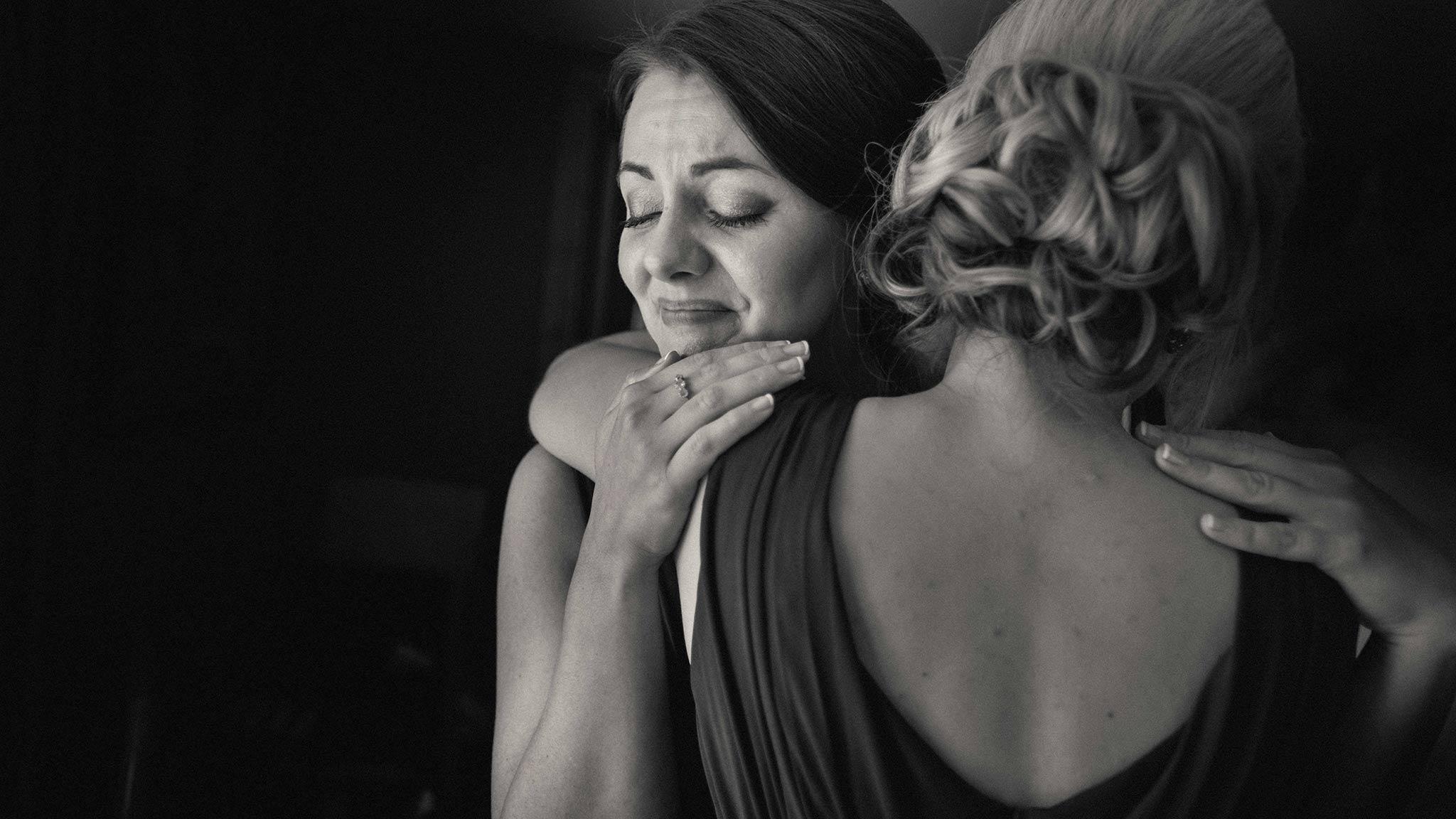 Bridesmaids emotionally hugging